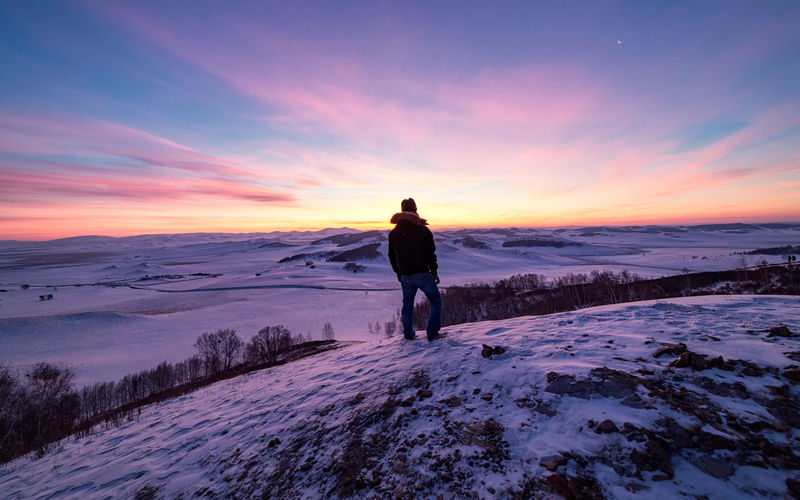 Rear view of man standing on snow covered land during sunset