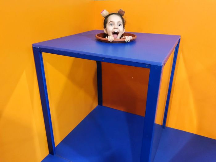 Optical illusion of girl head in plate on box during magic trick against yellow wall