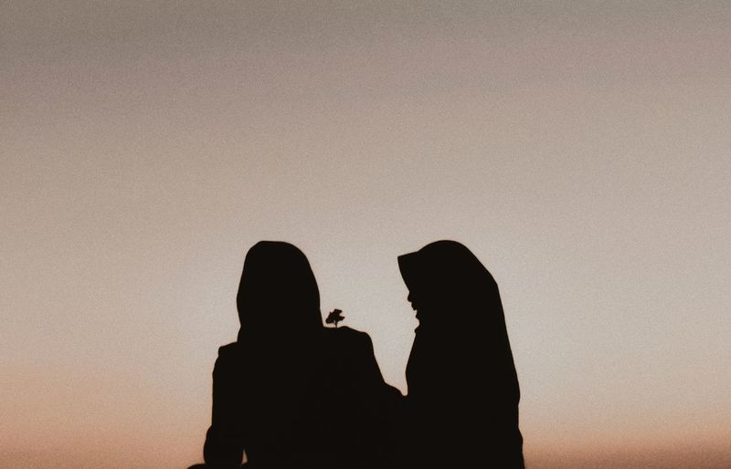 Silhouette female friends against clear sky during sunset