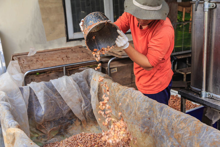 Midsection of man pouting cocoa seeds in container