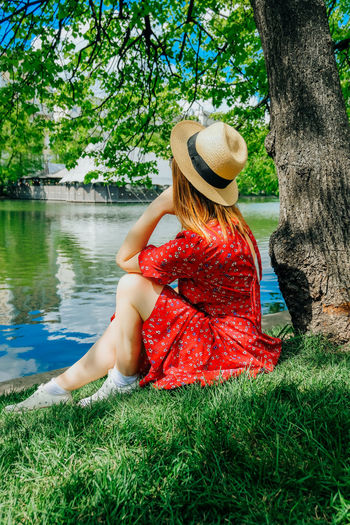 Woman sitting on grass by tree