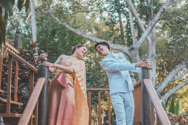 Young couple standing against trees