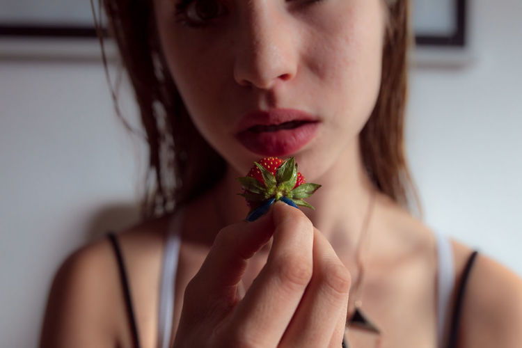 Close-Up Of Woman Holding Strawberry