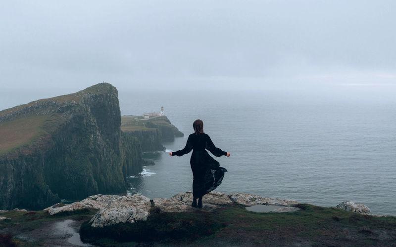 Woman in a black dress standing on rock by sea against sky, neist point scotland
