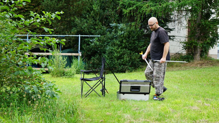 Man Holding Equipment While Walking At Grassy Field