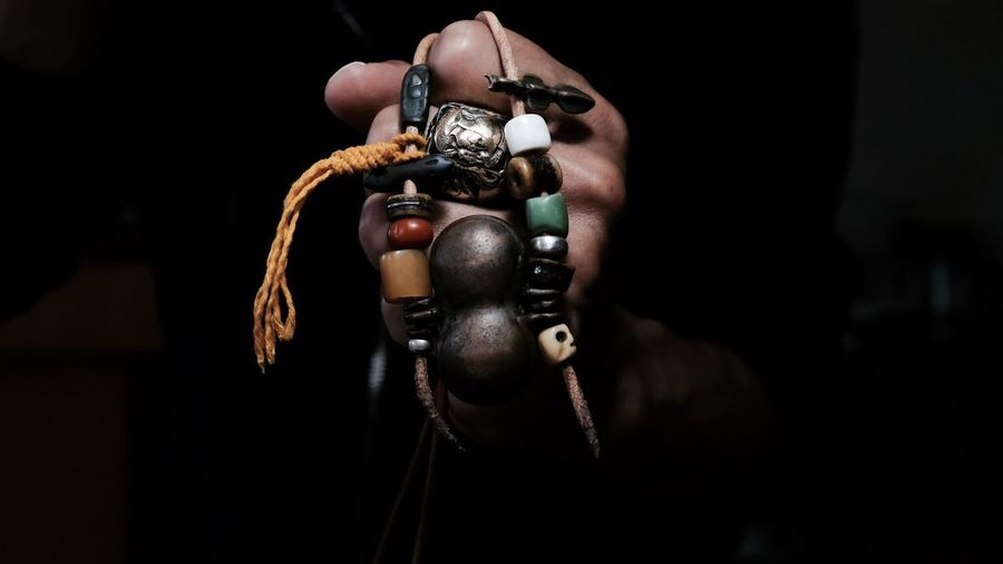 Cropped hand of man holding necklace
