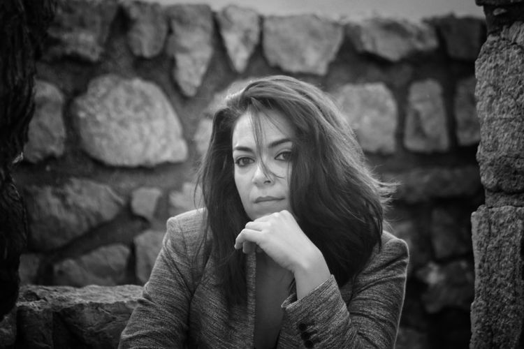 Portrait of woman sitting by stone wall