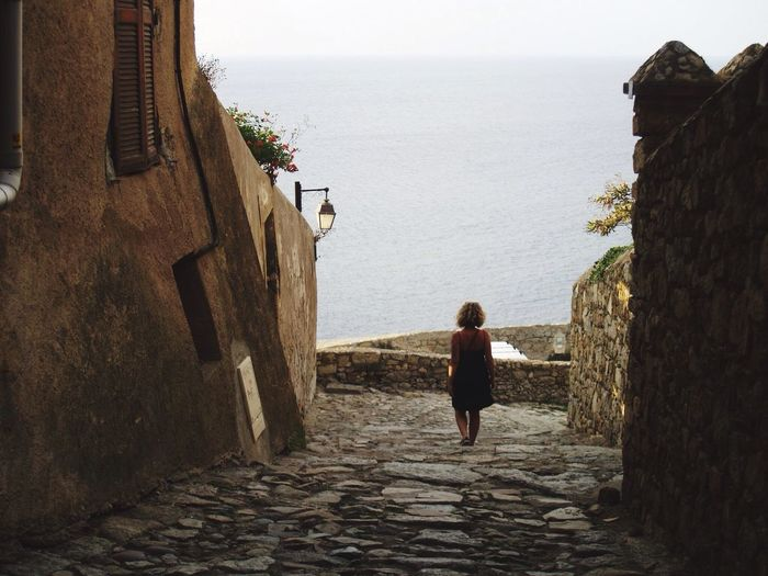 Rear view of woman walking in an old town by the sea
