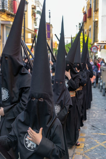 SEVILLE, SPAIN - MARCH 27: People dressed in all black for a Holy Week procession in Seville, Spain on March 27, 2018 Sevilla Seville SPAIN Day Europe European  Tourism Tourism Destination Travel Travel Destinations Easter Holy Week Semana Santa Parade Procession Black Jesus Jesus Christ People Crowd Float Nazareno Nazarenos Nazarene Nazarenes Real People Group Of People Unrecognizable Person Obscured Face Clothing Religion Catholicism Christianity Spirituality Christian Celebration