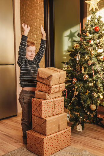 Cheerful boy with arms raised standing by christmas presents at home