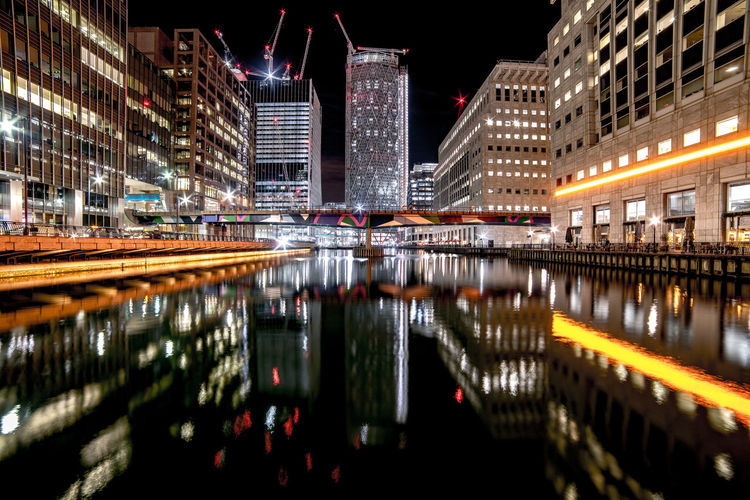 Reflection of illuminated buildings in river at night