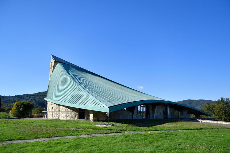 Barn on field against clear blue sky