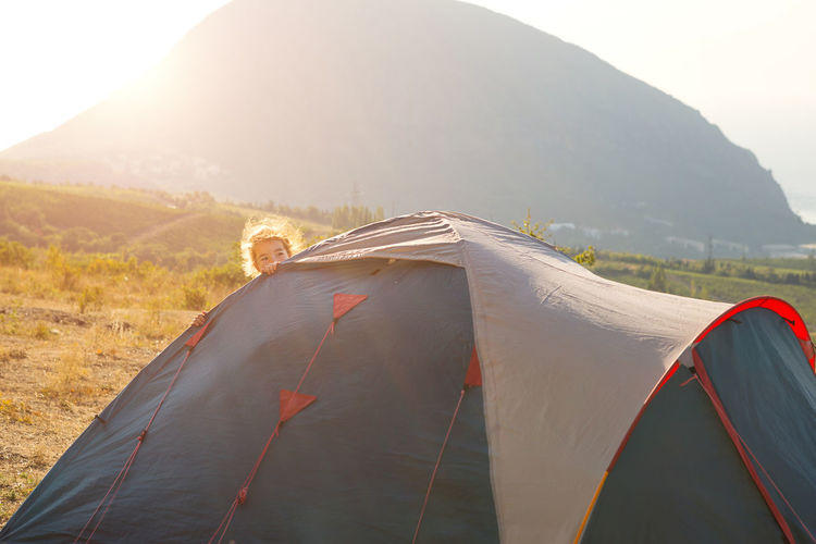 Cheerful child looks out from behind a tourist tent in the mountains with a panoramic view at dawn.