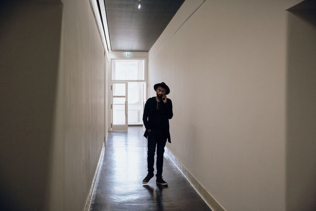 Business Corridors  Fashion Hallway Hat Meeting On The Phone... Working All Black Everything Backlit Corridor Day Direction Full Length Hall Indoors  Lifestyles Mens Fashion One Person Pacing People Real People Standing Talking On The Phone Young Adult