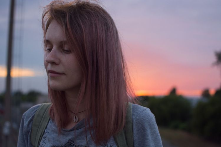 Portrait of woman looking away against sky during sunset
