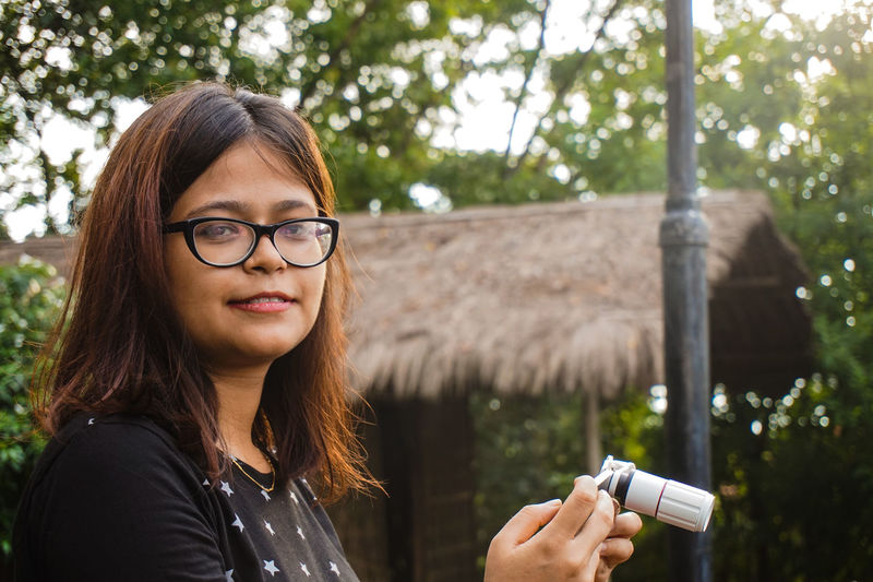 Portrait Of Smiling Woman With Smart Phone Standing Against Hut