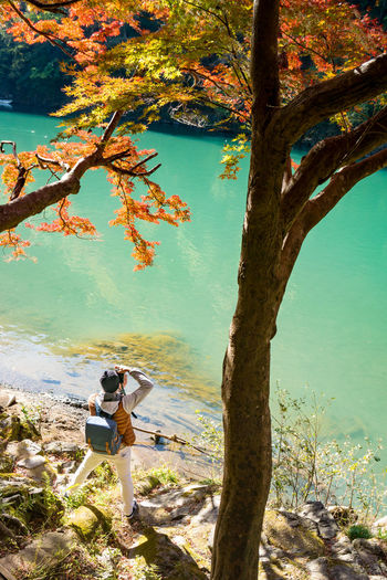 High angle view of man photographing while standing by tree at lakeshore