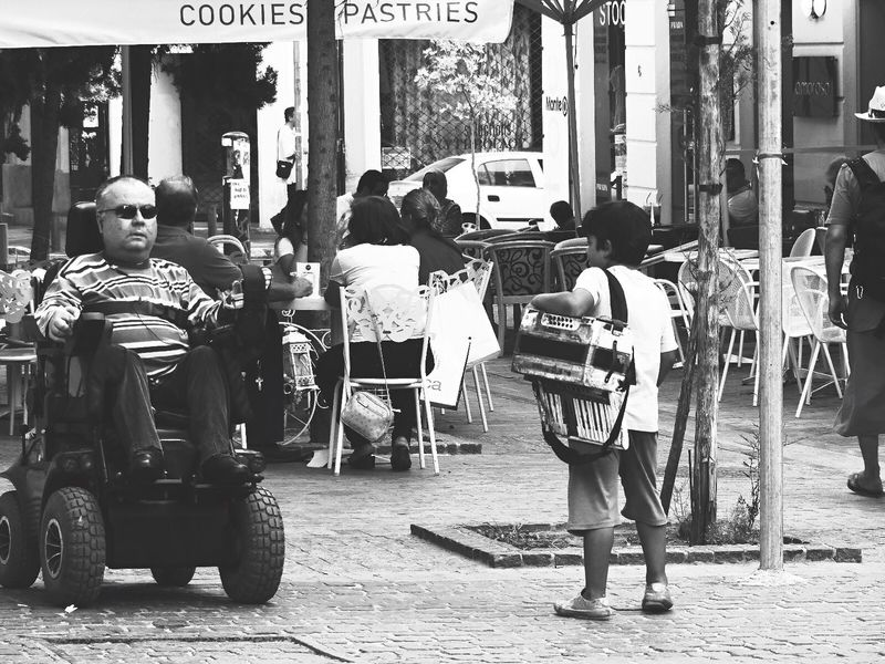 The curious kid At The Street of Athens, Greece | Street Photography Black And White Urban Lifestyle Black & White People Monochrome Boy Meets World Accordion Man On Cycle Wheelchair Capture The Moment Streetphoto_bw