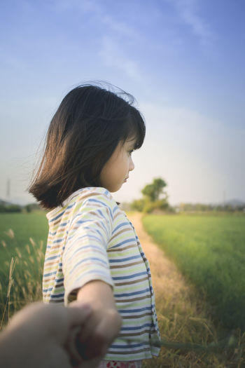 Thoughtful cute girl standing on grassy field against sky