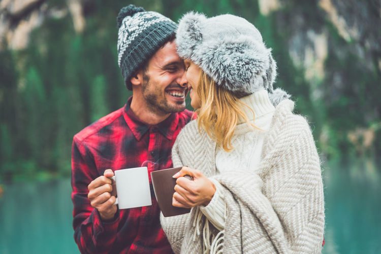 Close-up of couple holding coffee cup standing against lake