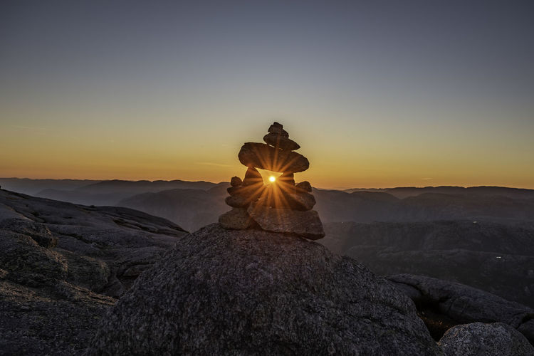 Man on rock against sky during sunset