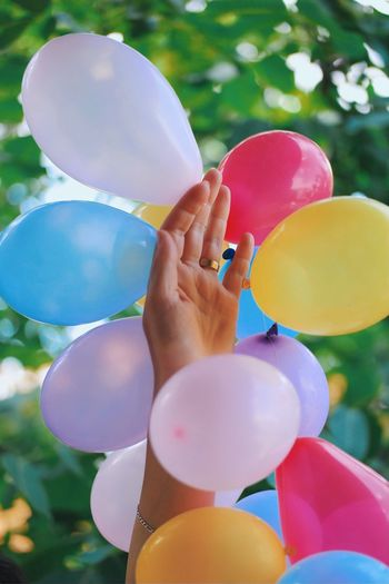 Cropped Hand Of Woman Amidst Colorful Balloons