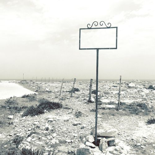 Road sign on snow covered land against sky