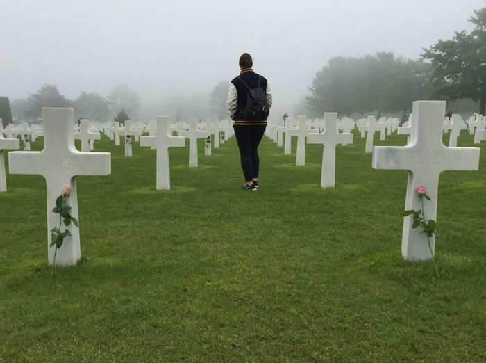 Rear view of woman walking at cemetery