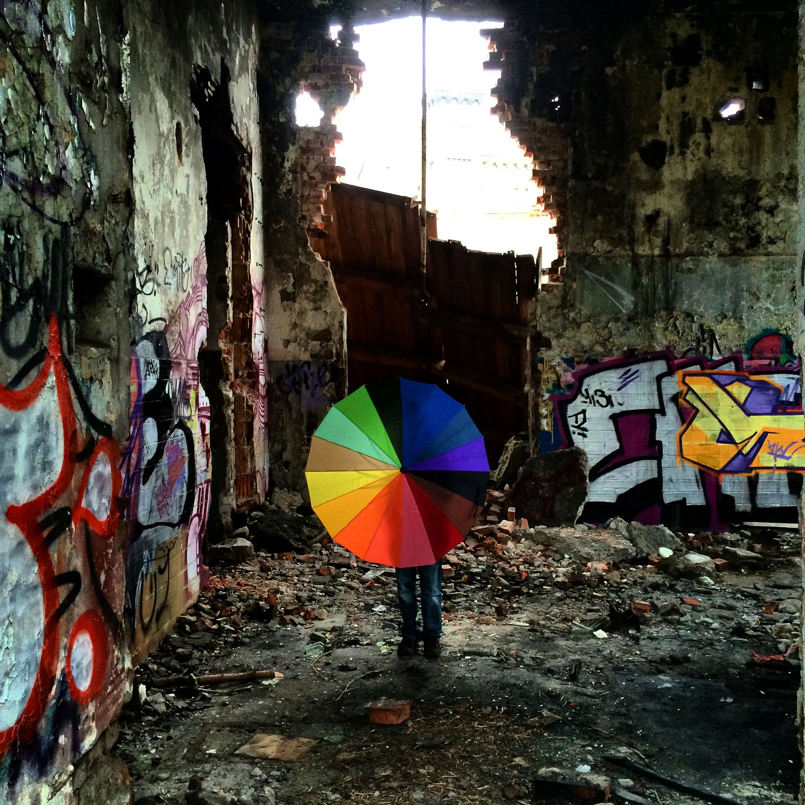 built structure, architecture, building exterior, graffiti, umbrella, day, multi colored, wall - building feature, building, flag, street, outdoors, sky, men, abandoned, tree, street art, hanging, yellow