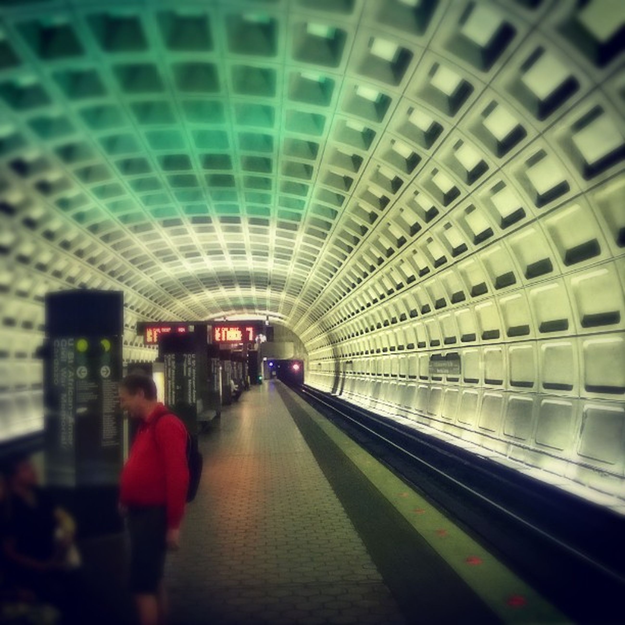 indoors, transportation, architecture, the way forward, built structure, walking, rear view, men, railroad station, railroad station platform, lifestyles, tunnel, diminishing perspective, travel, illuminated, public transportation, ceiling, full length