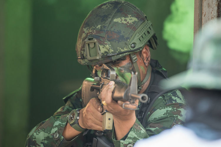 View of soldier holding rifle standing outdoors