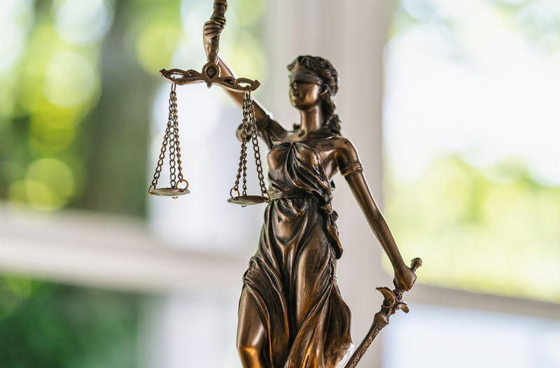 Close-Up Of Lady Justice Against Window