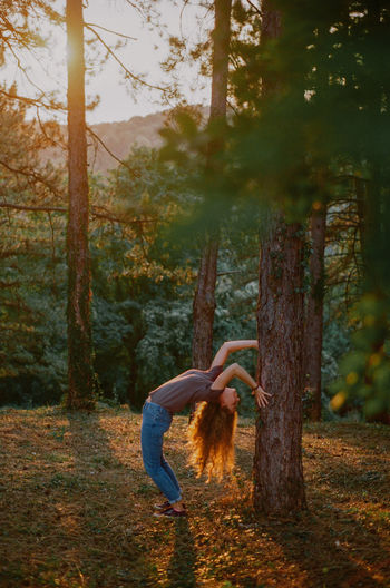 Side view of woman standing by tree in forest