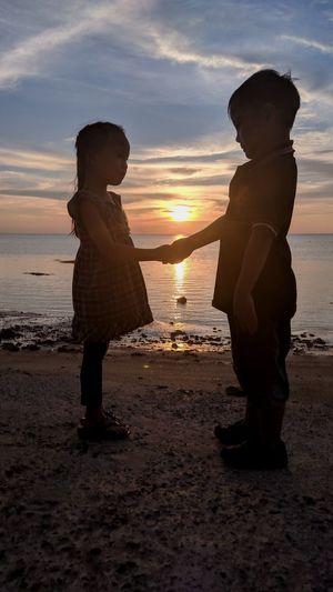 Full length of friends on beach against sky during sunset