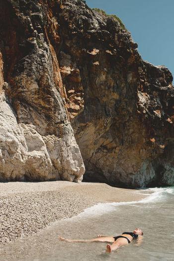Woman on rocks by sea