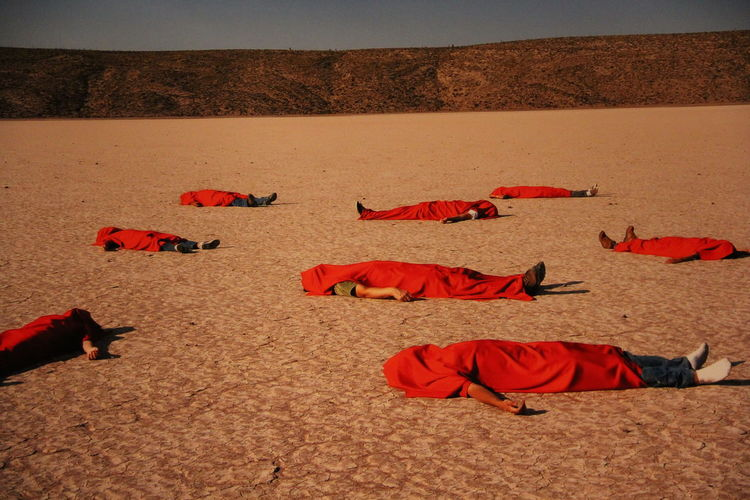 people covered in red fabric lying on land