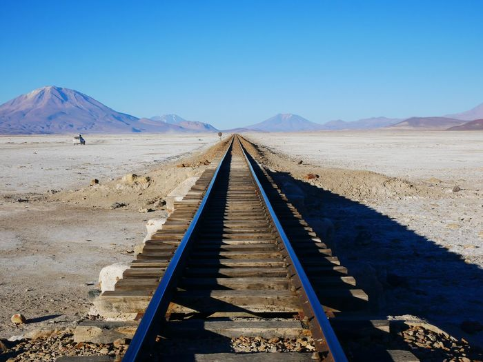 Scenic view of railroad track in desert against clear blue sky