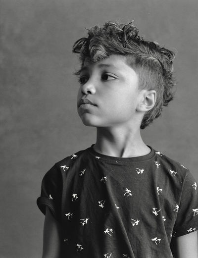 Boy looking away against wall at home