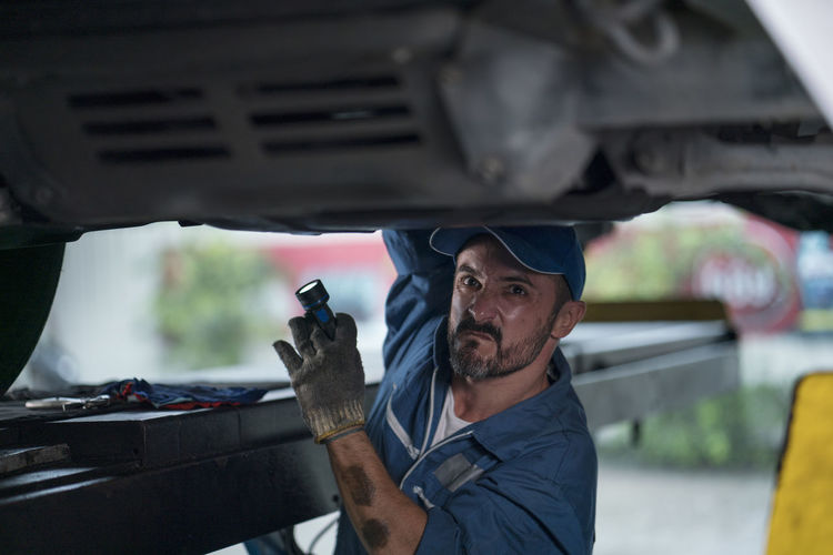 Portrait of man working on car