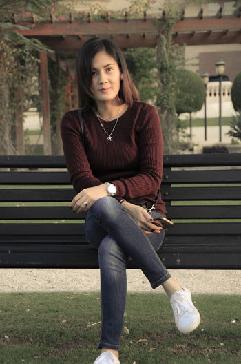Portrait Of Woman Sitting On Bench At Park