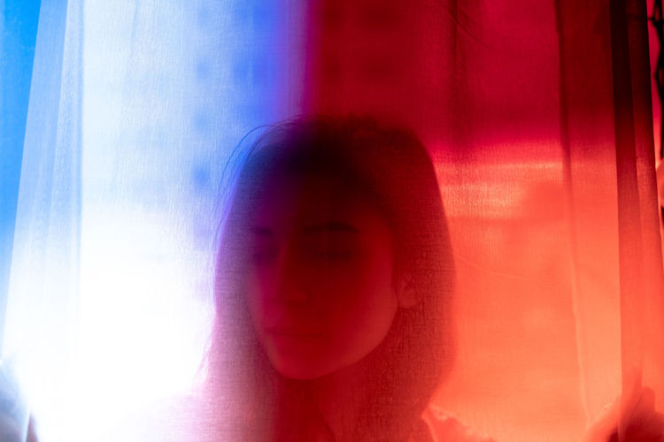 Close-up portrait of woman against window