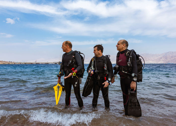 The Three Divers Dive Diver Sea And Sky Water Sea Leisure Activity Scuba Diving Aquatic Sport Lifestyles Wetsuit Adventure Real People Sport Standing Underwater Diving Underwater People Beach Men Eilat Israel