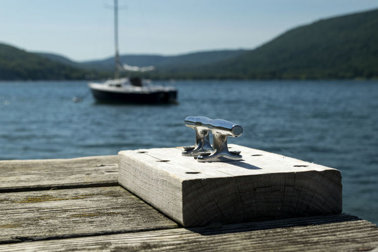 Cleat on pier by lake during sunny day
