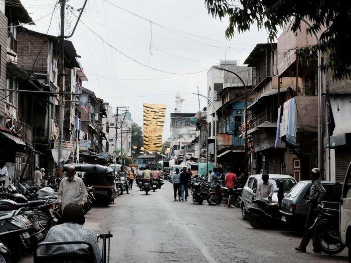 People walking on mahatma gandhi road amidst buildings against sky
