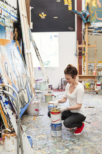 Happy artist crouching while dipping brush in paint can at art studio