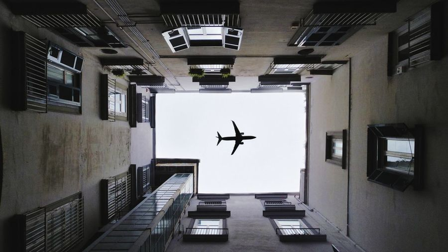 Directly below shot of airplane flying over buildings