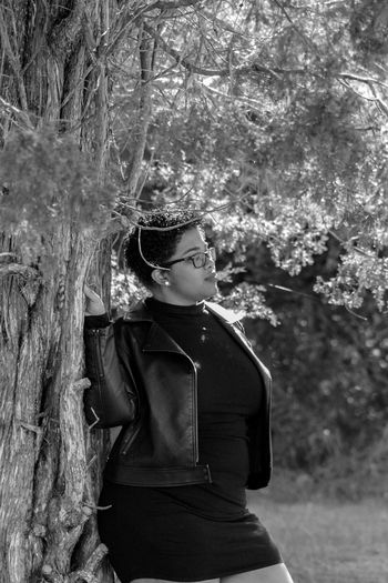 Tree One Person Real People Lifestyles Standing Tree Trunk Outdoors Nature Young Adult Young Women Pensive Black And White Leather Jacket Black Leather Jacket Black Dress Little Black Dress Short Hair Curly Hair Plus Size Model