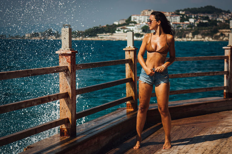 Beautiful Young Woman Removing Hot Pants While Standing On Pier Against Sea At Beach