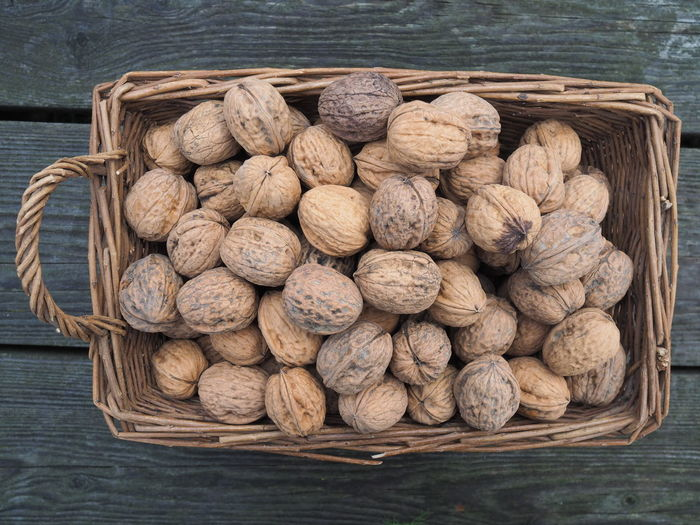 Directly above shot of walnuts in whicker basket on table