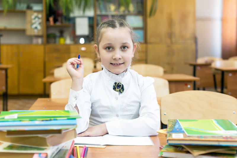 Portrait of girl sitting by books on table